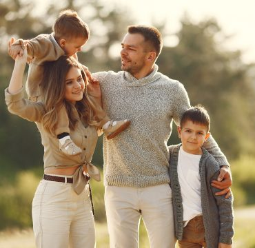 Family with cute little child. Father in a gray sweater. Sunset background.