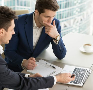Business partners using laptop while working together on important corporate project in office. Businessman attentively listening to adviser Investment specialist making presentation of promising deal
